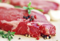 Two raw new york steaks on cutting board with thyme peppercorns and garlic
